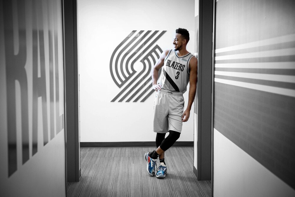 """Portland guard CJ McCollum shows off the Trail Blazers' new """"Earned"""" Edition uniform, which the team will debut Thursday against the Phoenix Suns. (Photo used with permission from Trail Blazers)"""