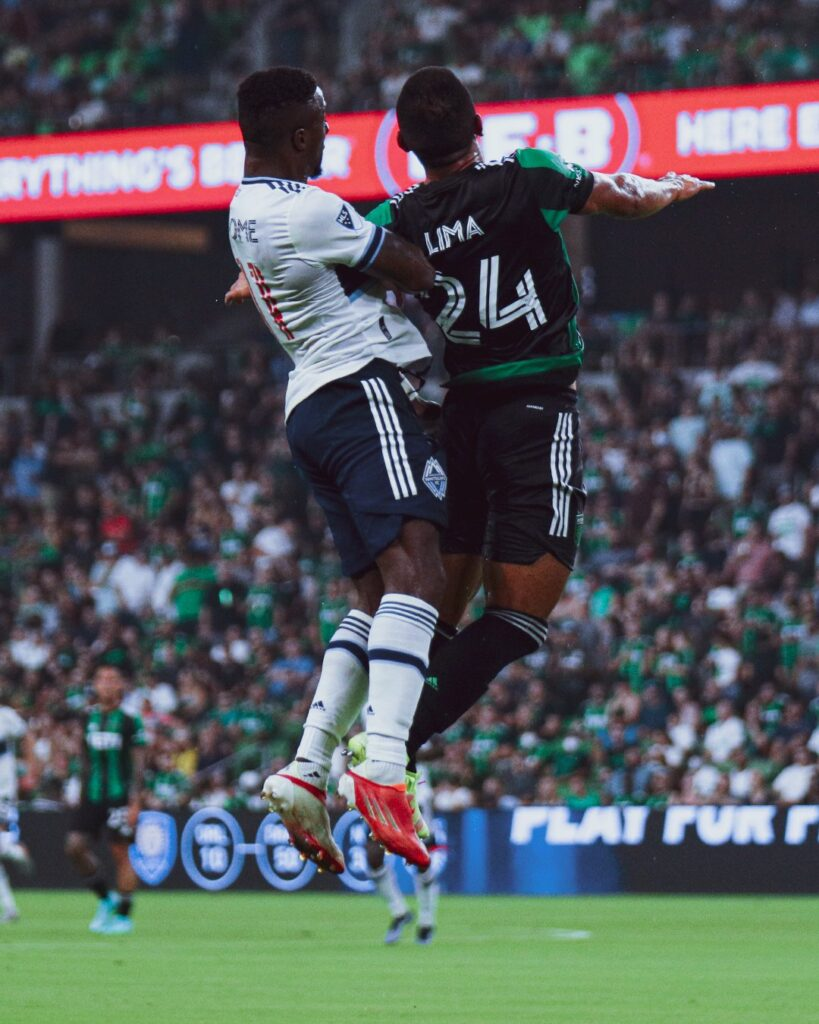 Whitecaps winger, Dajome, goes up for a 50/50 ball.